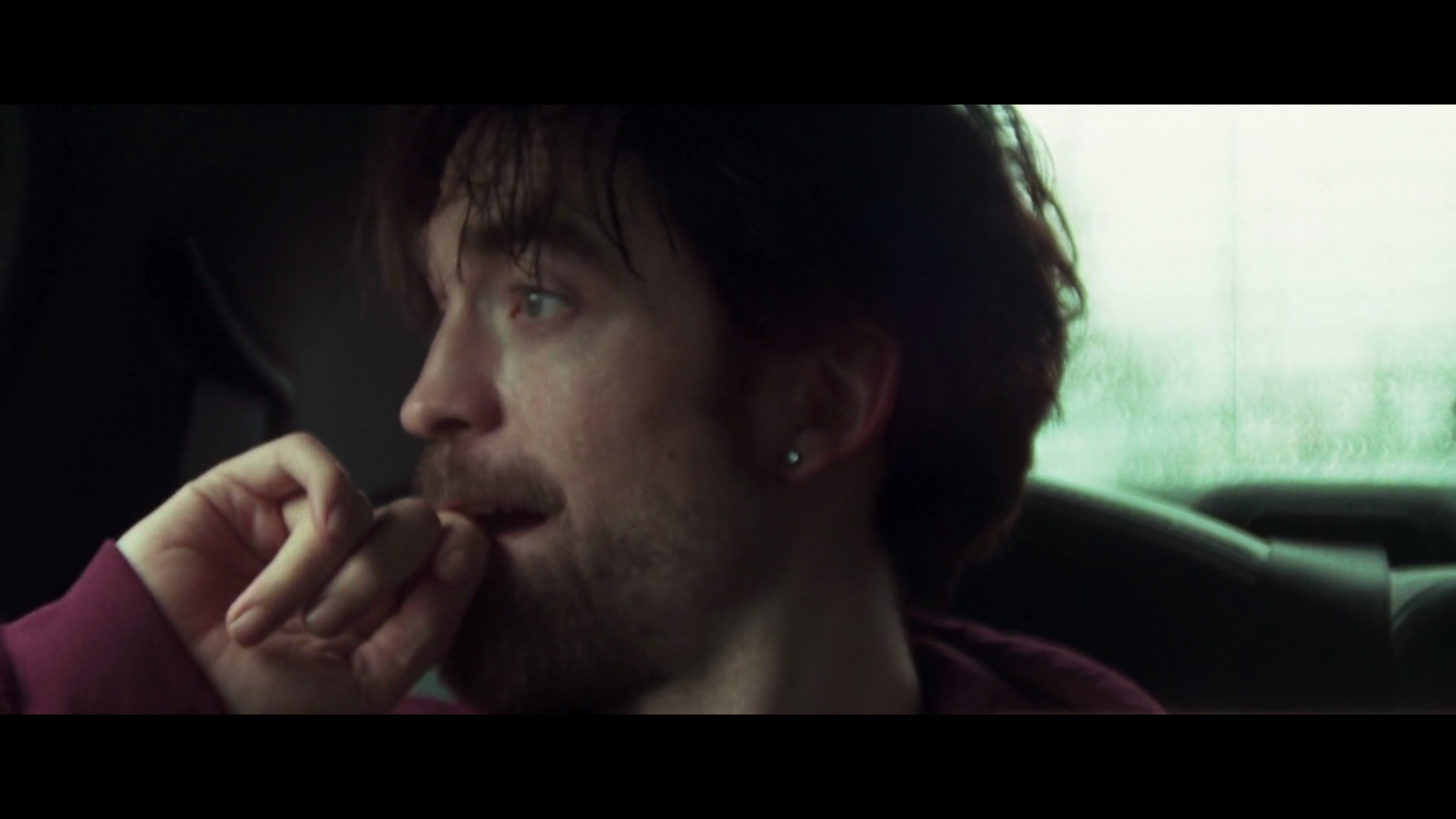 Robert Pattinson staring out car window in Good Time